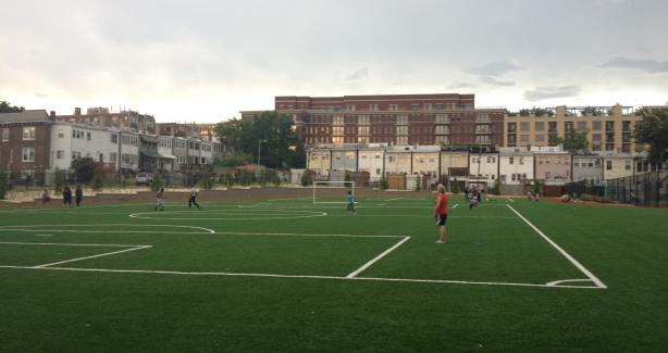 Photo of artificial grass soccer field with adults and children playing games on it.