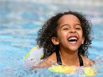 Little girl laughing and swimming in a pool