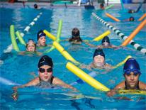 Group of children in a pool with colorful swimming aids